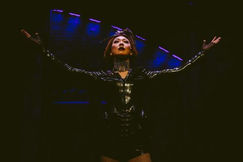 Madame Senneterre (Amy Kim Waschke) opens the show with a flourish. Her arms are spread wide, her face excited, her costume a kind of leather-mesh catsuit thing, topped with a floofy little purple hat with many protrusions. She is a middle-aged Asian woman.