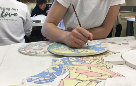Davan D. '21 paints on her ceramic piece
