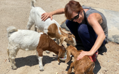 Ms. St John at her farm with her three goats, Rosie, Sissy, and Timmy
