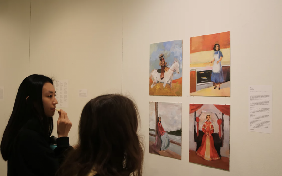 Vivian L. '20 and Max E. '21 observe Elisa D. '20's series of paintings.