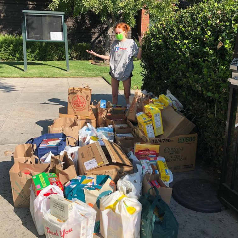 Mia+G.+%E2%80%9825+standing+in+front+of+piles+of+donated+breakfast+cereal+