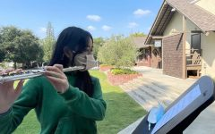 Outside of Braun, Crystal Z. '23 plays her flute with her specialized masks.